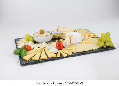 Various sorts of cheese on a black slate plate on white background