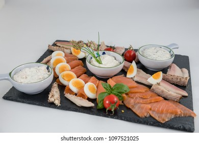 Various sorts of fish on a black slate plate on white background