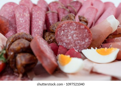 Various sorts of sausage decorated on a plate on white background