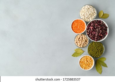 Various sources of vegetable protein: beans, lentils, peas, chickpeas, mung bean in bowls. A healthy balanced diet for vegans and vegetarians. Gray stone background. Flat lay, copy space