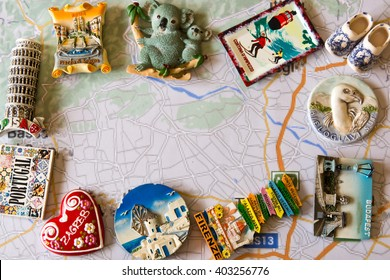 various souvenir magnets from several world country arranged on the auto map