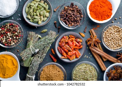 Various spices in glass bowls on a dark stone background, top view, horizontal image