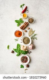 Various Spices, Herbs and Condiments on white stone table, top view, copy space. Healthy cooking, indian food background.