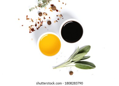 Various spices, herbs, olive oil and balsamic vinegar on a white background top view. Free space for text. Food background, ingredients for cooking.