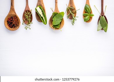 Various of spices and herbs on wooden background. Flat lay spices ingredients rosemary, thyme, oregano, sage leaves and sweet basil on white wooden.