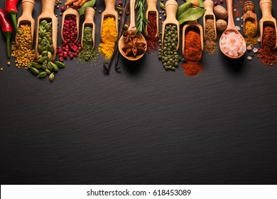 Various spices on black slate. Top view with free space