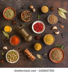 Various Spices on dark background. Assortment, set of spices and condiments with pepper mill, top view, flat lay. Cooking food concept.