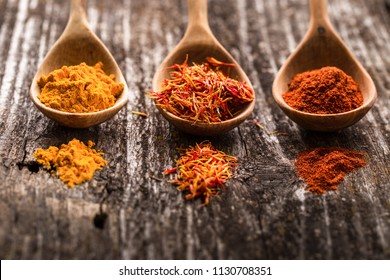 Various spices on wooden spoons. Saffron, turmeric and paprika. Food ingredients for cooking.  Banners of herbs and spices. Space for text