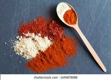 Various spices red pepper, paprika, seasoning, turmeric, ginger powder in a wooden spoon. View from above. indian spices on dark gray background