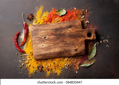 Various spices spoons and cutting board on stone table. Top view with copy space