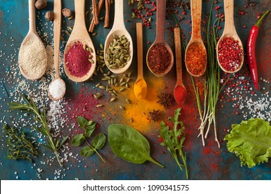 Various spices spoons and herbs on a blue background. Top view
