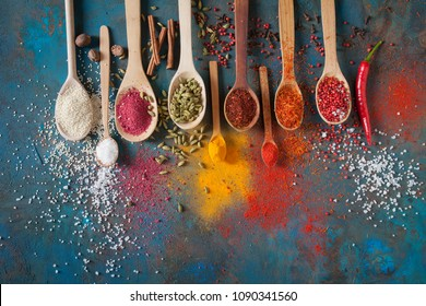 Various spices spoons on a blue background. Top view