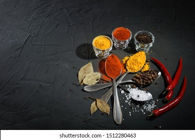 Various spices spoons on stone table.On dark concrete background.Herbs and spices on wooden table.  Top view with space for your text