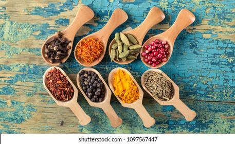 Various spices in wooden spoons on rustic wooden background. Assortment of colorful spices. Food ingredients, top view