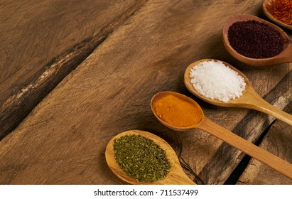 Various spices in wooden spoons on a old wooden rustic table. Colored oriental spices in spoons