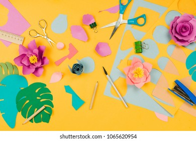 Various stationary supplies, colored paper, papercraft flowers on yellow background. Concept of creativity or art, flatlay