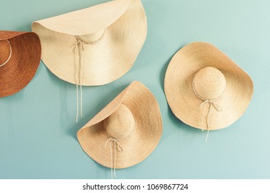 Various summer hats hanging on the pastel color wall, basketwork hat for decoration in house.