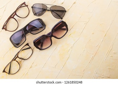 Various sunglasses set on yellow wooden background with empty space.