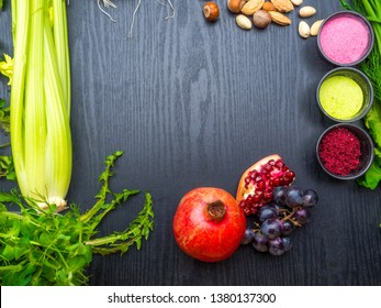 various Super foods, berry powder - strawberry, raspberry, nuts, pomegranate, grape, dandelion and selery, broccolion a wooden background, copy space