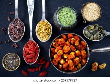 Various superfoods on black background
