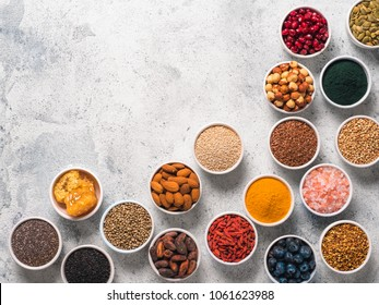 Various superfoods in smal bowl gray concrete background. Superfood as chia, spirulina, raw cocoa bean, goji, hemp, quinoa, bee pollen, black sesame, turmeric. Copy space for text. Top view, flat-lay.