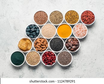 Various superfoods in smal bowl gray concrete background. Creative layout of superfood as chia, spirulina, raw cocoa bean, goji, hemp, quinoa, bee pollen, black sesame, turmeric. Top view or flat-lay.