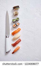 Various sushi rolls with Japanese knife on white stone slate background. With copy space for text. Top view.