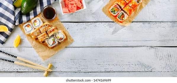 Various Sushi Set Background, Frame or Mockup on Rustic Wooden Desk Top View with Place for Text. Nori Maki, Norimaki or Futomaki Restaurant Collection for Menu Template on Old Painted Table Flat Lay