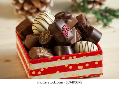 Various of sweet confectionery with chocolate candies and pralines in beautiful package on wood background