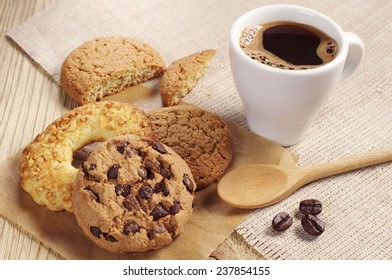 Various sweet cookies and cup of hot coffee on wooden table