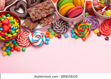 Various sweets assortment. Candy, bonbon and macaroons on pink background. Top view with copy space