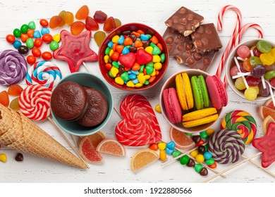 Various sweets assortment. Candy, bonbon, chocolate and macaroons over wooden background. Top view flat lay