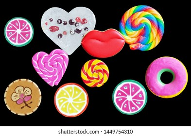 Various sweets and gingerbread in the shape of lips, on a black background