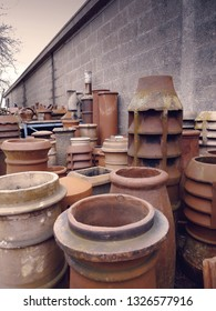 Various terracotta chimney stacks at a salvage yard in the UK.