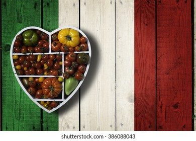 Various tomatoes in heart shaped box on wooden background painted in colors of italian flag. Fresh homegrown organic food. Love for mediterranean, Italian food. Some negative space