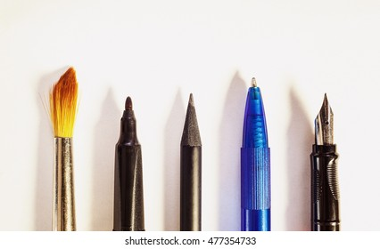Various tools for writing or painting, conceptual composition on white paper.