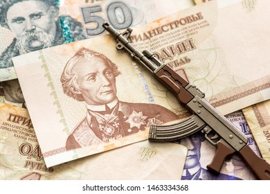 various transnistrian ruble banknotes and kalashnikov ak47 assault rifle war conflict concept