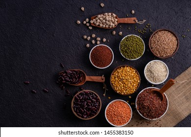 Various type of cereal grains, rice,brown rice, buckwheat, barley, ,millet. Various raw uncooked grains on dark background pulses, grains, seeds and millet.