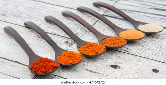 Various type of chili powder in wooden spoon over wooden background
