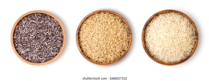 Various type and color of rice ;  riceberry, brown coarse rice and white thai jasmine rice in wooden bowl isolated on white background. Healthy food concept. Flat lay. Top view.