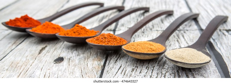 Various type of hot and spicy chili and peppercorn powder in wooden spoon over wooden background