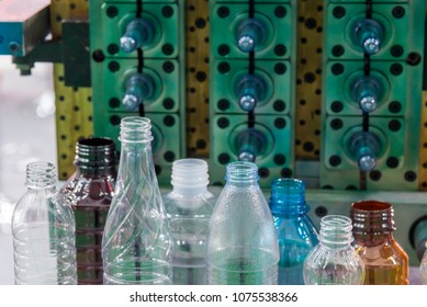 The various type of plastic bottle product with injection mold background.Drinking container manufacturing processing.