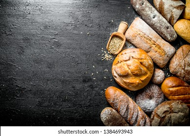 Various types of bread with grain. On black rustic background