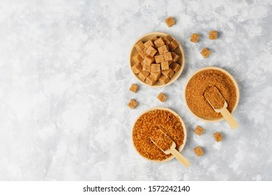 Various types of brown sugar on concrete background,top view