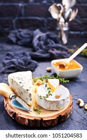 Various types of cheese, blue cheese and brie with honey and nuts