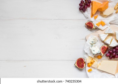 Various types of cheese with fruits on the wooden white table with copy space. Top view.