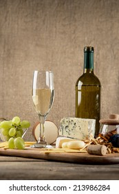 Various types of cheese, grapes, honey,  bottle of wine  composition