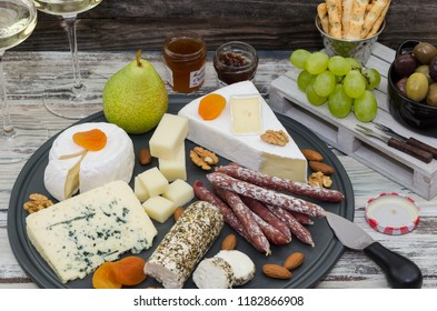 Various types of cheese. Cheese and meat appetizer selection. Wine snack set. Variety of cheese, salami, fruits, olives, nuts on a rustic wooden background