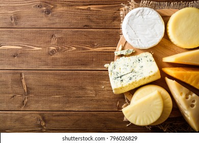 Various types of cheese on dark rustic wooden background. Top view. Copy space.