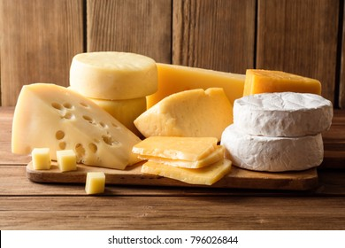 Various types of cheese on dark rustic wooden background. Selective focus.